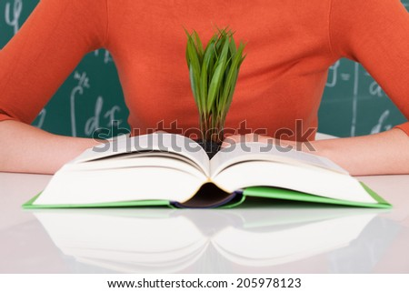 Midsection of young college student with book and sapling at desk in classroom - stock photo