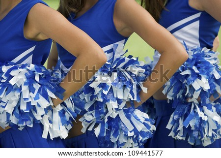Midsection of young female cheerleaders holding pom-poms - stock photo