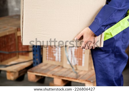 Midsection of young foreman in uniform carrying cardboard box at warehouse - stock photo
