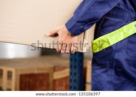 Midsection of young foreman in uniform carrying cardboard box in warehouse - stock photo