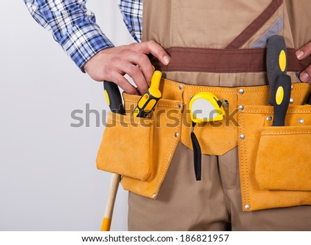 Midsection of young foreman wearing tool belt - stock photo