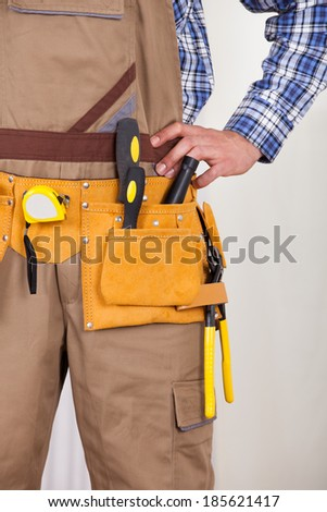Midsection of young male repairman wearing tool belt at home - stock photo