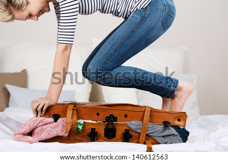 Midsection of young smiling woman packing suitcase on bed - stock photo