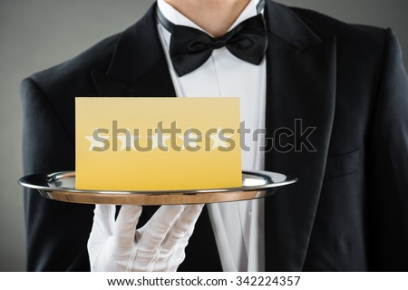 Midsection of young waiter holding tray with star rating label against gray background - stock photo