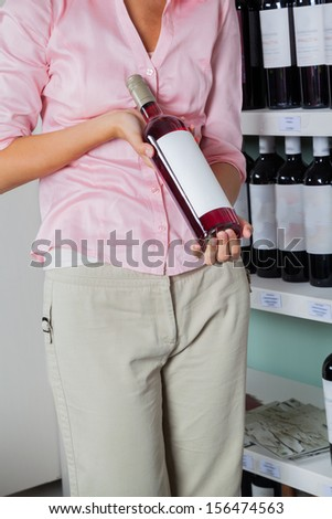 Midsection of young woman holding wine bottle in supermarket - stock photo