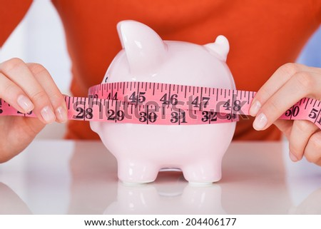 Midsection of young woman measuring piggybank with measure tape at desk - stock photo