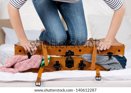 Midsection of young woman packing suitcase on bed - stock photo