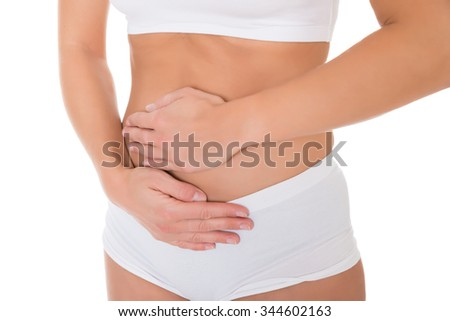 Midsection of young woman suffering from stomach pain over white background - stock photo