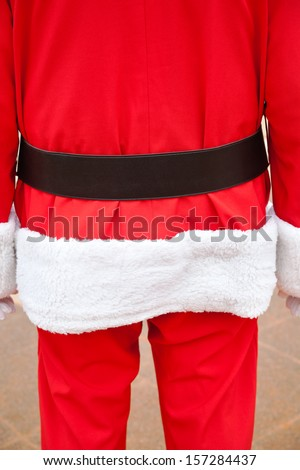 Midsection rear view of senior man in Santa Claus costume standing outdoors - stock photo