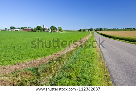 Midwest American farmland with long road and fields - stock photo