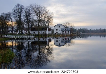 Midwinter light at the lake before the sunrise - stock photo