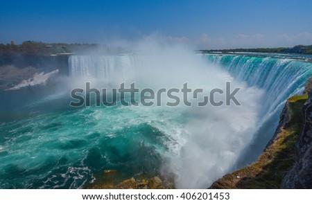Mighty Niagara River roars over the edge of the horseshoe falls in Niagara Falls Ontario.  Misty foggy spray rises up. - stock photo