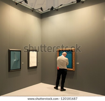 MILAN - APRIL 08: A man looks at paintings galleries during MiArt, international exhibition of modern and contemporary art on April 08, 2011 in Milan, Italy - stock photo