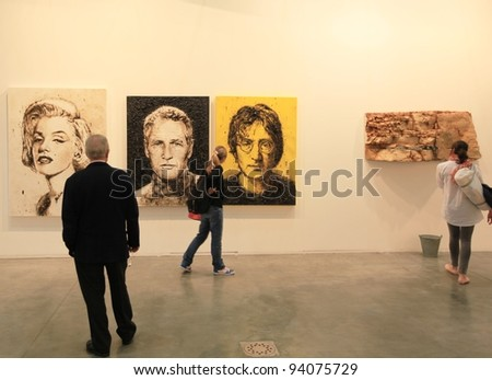 MILAN - APRIL 08: People look at paintings dedicated to Marilyn Monroe, Paul Newman and John Lennon at MiArt, international exhibition of modern and contemporary art on April 08, 2011 in Milan, Italy. - stock photo