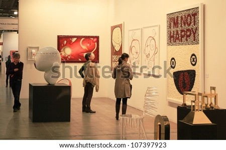 MILAN - APRIL 08: People look at paintings galleries at MiArt, international exhibition of modern and contemporary art on April 08, 2011 in Milan, Italy. - stock photo