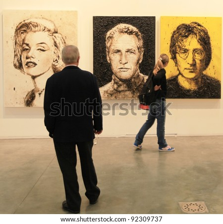 MILAN - APRIL 08: People look at paintings galleries during MiArt, international exhibition of modern and contemporary art on April 08, 2011 in Milan, Italy - stock photo