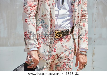 MILAN - FEBRUARY 20: Man poses for photographers with pink Gucci floral suit and belt before Gucci fashion show, Milan Men's Fashion Week street style on June 20, 2016 in Milan. - stock photo