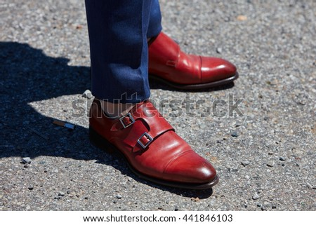 MILAN - FEBRUARY 20: Man poses for photographers with red leather shoes and blue trousers before Gucci fashion show, Milan Men's Fashion Week street style on June 20, 2016 in Milan. - stock photo