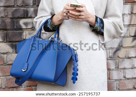 MILAN - FEBRUARY 26: Woman poses for photographers before Fendi show with Fendi blue bag Milan Fashion Week Day 2, Fall/Winter 2015/2016 street style on February 26, 2015 in Milan. - stock photo