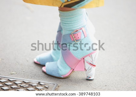 MILAN - FEBRUARY 25: Woman poses for photographers with blue and pink shoes and socks before Fendi fashion show, Milan Fashion Week Day 2 street style on February 25, 2016 in Milan. - stock photo
