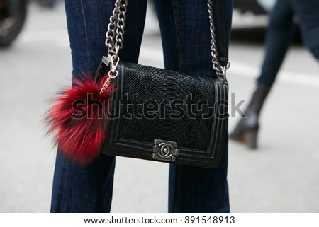 MILAN - FEBRUARY 26: Woman poses for photographers with Chanel black snake bag with Fendi fur accessory before Etro fashion show, Milan Fashion Week Day 3 street style on February 26, 2016 in Milan. - stock photo