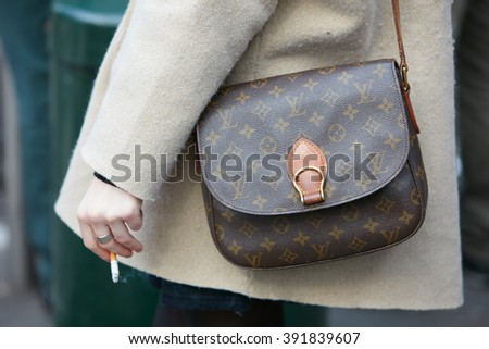 MILAN - FEBRUARY 26: Woman poses for photographers with Louis Vuitton bag and cigarette before Emporio Armani fashion show, Milan Fashion Week Day 3 street style on February 26, 2016 in Milan. - stock photo