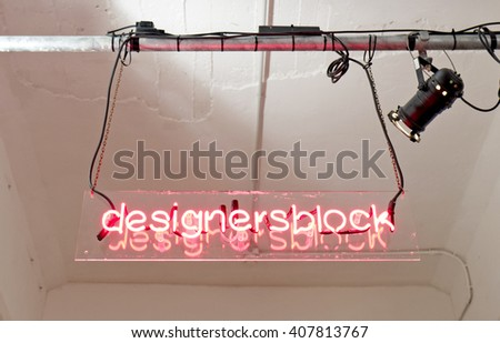 MILAN, ITALY-APRIL 12, 2016: neon sign of the design exhibition at Base co working space, during the Fuori Salone of the International Design Week Salone del Mobile, in Milan. - stock photo