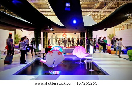 MILAN, ITALY - APRIL 15: People look at living room interiors design solution at Salone del Mobile, international furnishing accessories exhibition April 15, 2010 in Milan, Italy.  - stock photo