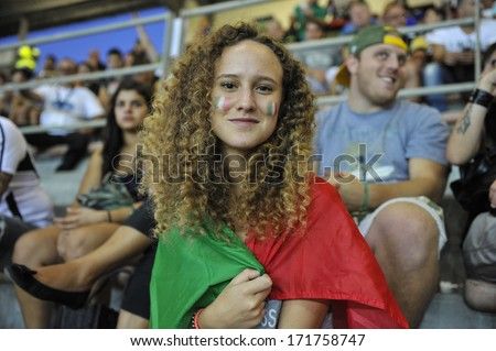 MILAN, ITALY - AUGUST 31: an italian girl wearing the national flag supports the national team during the American Football European Championship match Italy vs Spain in Milan AUGUST 31, 2013. - stock photo
