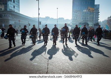 MILAN, ITALY - DECEMBER 10: Police follows demonstrators protesting against government and politicians on DECEMBER 10, 2013 in Milan. - stock photo