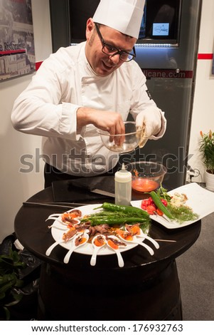 MILAN, ITALY - FEBRUARY 13: Cook prepares finger food at Bit, international tourism exchange reference point for the travel industry on FEBRUARY 13, 2014 in Milan. - stock photo