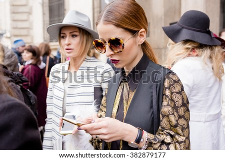 MILAN, ITALY - FEBRUARY 25, 2016: Fashionable woman attending models and vips using smartphone in the streets during Milan Fashion Week Women Fall/Winter 2016/2017 - stock photo