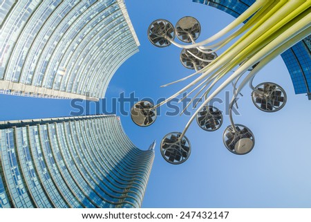 MILAN, ITALY - January 25, 2015: Architectural detail of the glass facade on the building tower Unicredit in Milan, the tallest skyscraper in Italy. View from below with a light pole in the middle. - stock photo