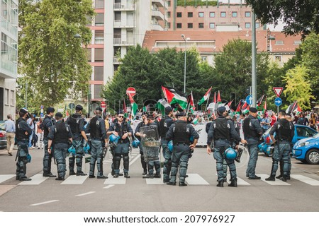 MILAN, ITALY - JULY 26: Riot police follows people marching and protesting against Gaza strip bombing in solidarity with Palestinians on JULY 26, 2014 in Milan. - stock photo