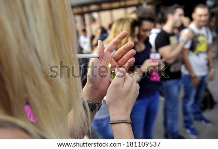 MILAN, ITALY-JUNE 20, 2012: College student's girl smoking a cigarette, before entering at school for the secondary school's final exams, at the Artemisia Gentileschi School in Milan. - stock photo