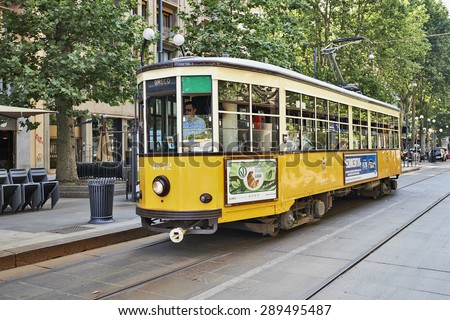 MILAN, ITALY- JUNE 11, 2015: Old vintage yellow tram and his driver on the street of Milan, Italy . Symbol of mobility, ecology and alternative energy - stock photo