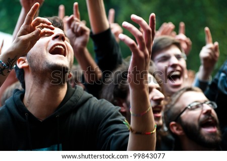 MILAN, ITALY - JUNE 10: unidentified group of people cheer during the Mi Ami music festival in Milan on June 10, 2011. The Mi Ami festival is held annually each June in Milan. - stock photo