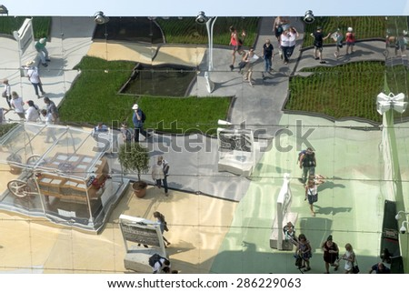 MILAN, ITALY-JUNE 05, 2015: visitors reflected on the the modern mirror architecture of the Basmati rice pavillon at EXPO 2015, in Milan. - stock photo
