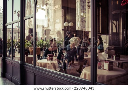 MILAN, ITALY - MARCH 5, 2014: People eating at small cafe at Galleria Vittorio Emanuele II shopping mall in Milan. Toned picture - stock photo