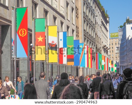 MILAN, ITALY - MARCH 28, 2015: Tourists walking by the flags from all countries of the world on show in Milan city centre as part of the Expo Milano 2015 international exhibition - stock photo