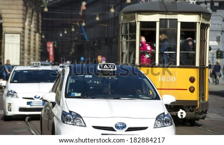 MILAN, ITALY-MARCH 19, 2014: White taxi cabs, and orange vintage tram, at work in downtown Milan. - stock photo