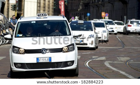 MILAN, ITALY-MARCH 19, 2014: White taxi cabs at work in downtown Milan. - stock photo
