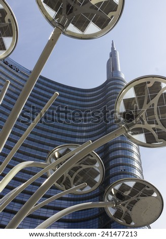 MILAN, ITALY - MAY 10 2014: Architectural detail of the glass facade on the Unicredit tower building in Milan, the tallest skyscraper in Italy. View from the bottom with a light pole in the middle - stock photo