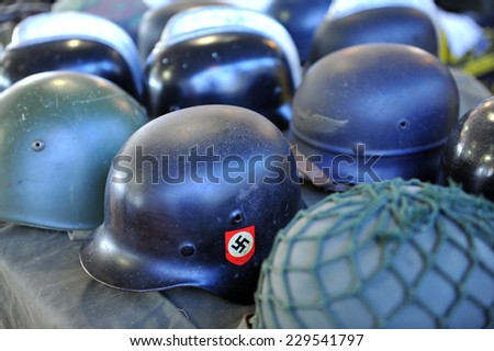 MILAN, ITALY - NOV 1: Military Nazism helmets, Exhibitor sitting in his stand at Militalia, exhibition dedicated to militaria collectors and military associations on November 1, 2014 in Milan. - stock photo