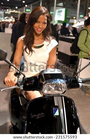 MILAN, ITALY - NOV 8: Model at stand Piaggio Vespa at EICMA, 72 th International Motorcycle Exhibition November 8, 2014 in Milan, Italy. - stock photo