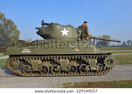 MILAN, ITALY - NOV 1: Old military tank, Exhibitor sitting in his stand at Militalia, exhibition dedicated to militaria collectors and military associations on November 1, 2014 in Milan. - stock photo