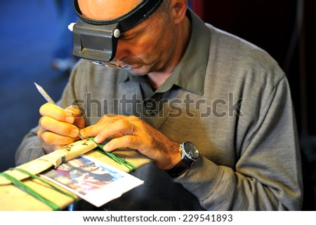 MILAN, ITALY - NOV 1: Scoring Knife, Exhibitor sitting in his stand at Militalia, exhibition dedicated to militaria collectors and military associations on November 1, 2014 in Milan. - stock photo