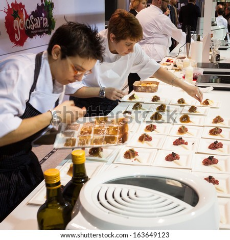 MILAN, ITALY - NOVEMBER 18: Chef's assistants work at Golosaria, important event dedicated to culture and tradition of quality food and wine on NOVEMBER 18, 2013 in Milan. - stock photo