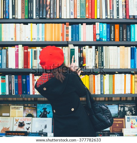 MILAN, ITALY - NOVEMBER 20, 2015: Rear view of a woman choosing a book on a shelves in a book shop - stock photo