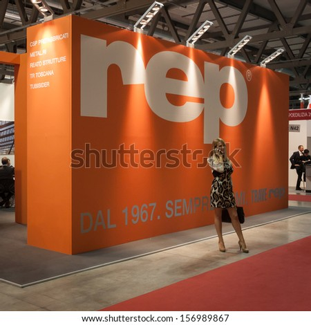 MILAN, ITALY - OCTOBER 3: A beautiful woman talks on phone at Made expo, international architecture and building trade show on OCTOBER 3, 2013 in Milan. - stock photo